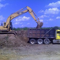 Excavator filling dump truck with dirt